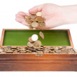 Hand dropping coins in a treasure chest — Stock Photo
