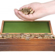 Hand full of coins over a treasure chest — Stock Photo