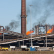 Stock Photo: Steel factory with smokestack and gas flaring