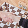 Royalty-Free Stock Photo: Shaking hands by a chess match