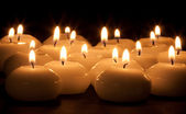Group of burning candles at a black background — Stock Photo