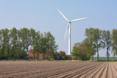 Farmhouse with a windturbine — Stock Photo