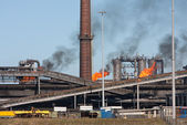 Steel factory with smokestack and gas flaring — Stockfoto
