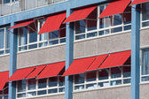Facade of a building with red sunshades — Stok fotoğraf