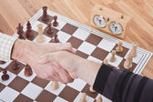 Shaking hands by a chess match — Stock Photo