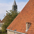 Old dutch historic farmhouse with churchtower behind it — Stock Photo