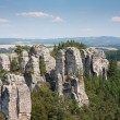 Sandstone pillars arising above the wood in the Czech republic - Stock Photo