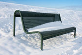 Green iron bench covered by snow in wintertime — Stock Photo