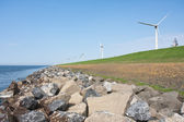 Endless dike with windmills with lonely bicycle — Stock Photo