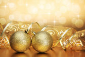 Christmas background with golden baubles, ribbon and bokeh — Stock Photo