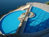 A turquoise blue resort hotel swimming pool — Foto de Stock