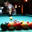 close up of pool table and balls pictured mid game under billiard hall ligh — Stock Photo
