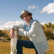 Eccentric man leaning to a fence post — Stock Photo #7487602