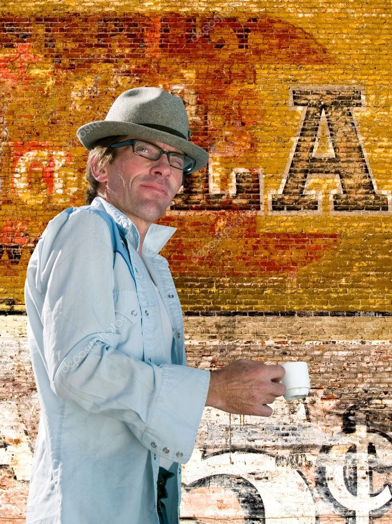 Man enjoying an afternoon espresso, wearing a western shirt and a fedora, against an old brick wall  Stock Photo #7487224