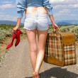 Girl walking on a dirt road with a suitcase - Foto Stock