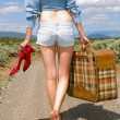 Royalty-Free Stock Photo: Girl walking on a dirt road with a suitcase