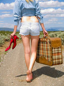 Girl walking on a dirt road with a suitcase — Stock Photo