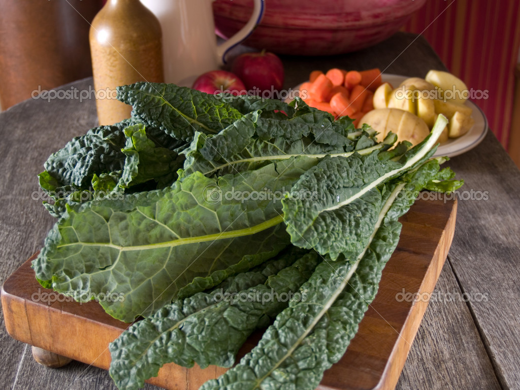 Lacinato kale on a wooden cutting board with other vegetables in the background — Stock Photo #7496731