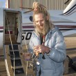 Eccentric senior man smiling by an aircraft holding key — Stock Photo