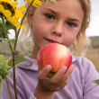 Little girl holding an apple - Stockfoto