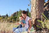 Mother and son goofing under a big pine tree — Stock Photo