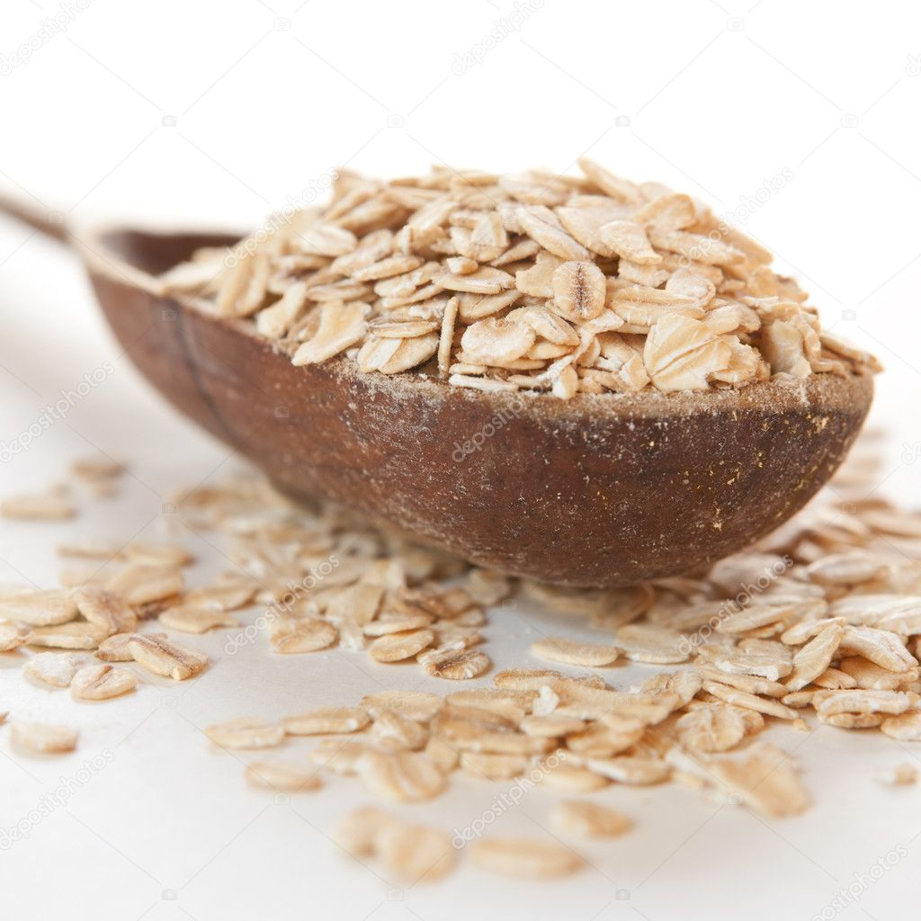 Raw thick rolled oats in a wooden spoon — Stock Photo #7553516