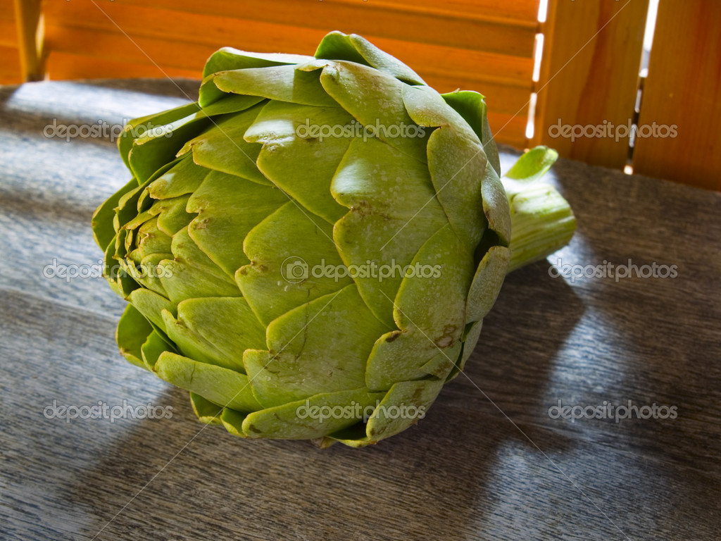 Artichoke on a rustic counter by the kitchen window — Stock Photo #7625593