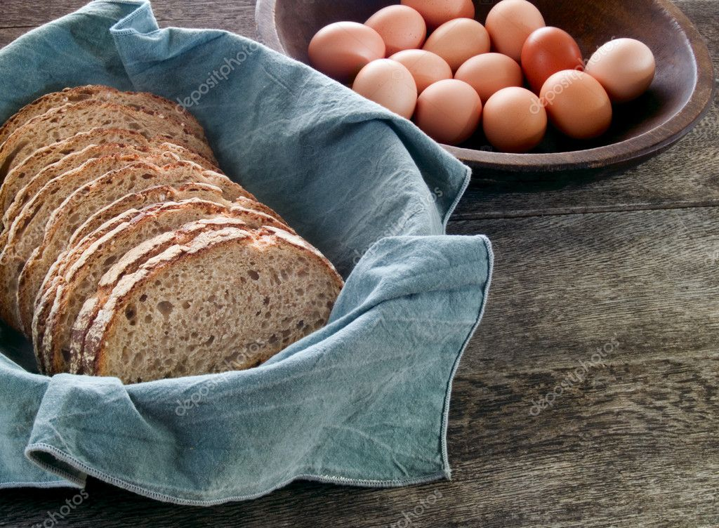 Fresh whole wheat bread in a basket with brown eggs in the background on a rustic wooden table  Stock Photo #7625640