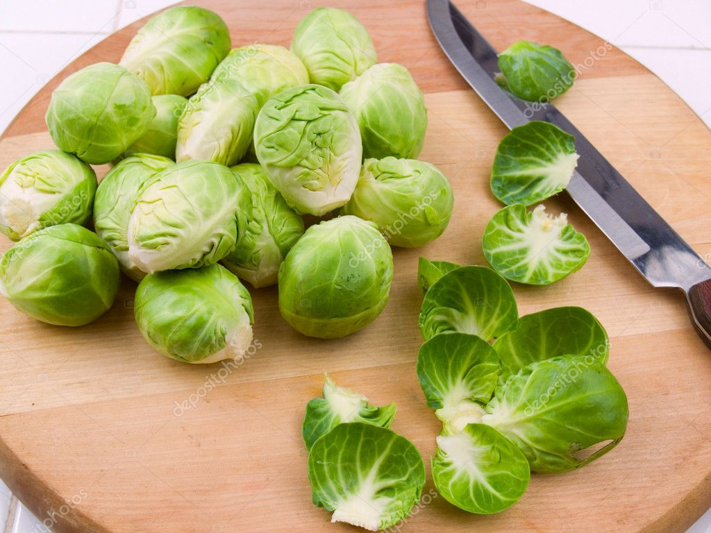 Fresh brussel sprouts on a wooden cutting board — Stock Photo #7625647