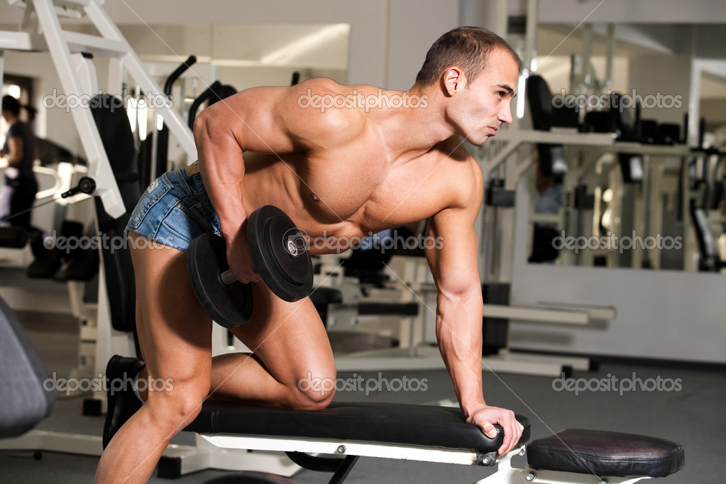 Young bodybuilder training in the gym: back - dumbell rows -finish position — Stock Photo #7575190