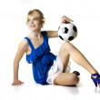 Blond girl in a blue dress with soccer ball — Stock Photo