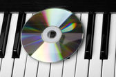 Unidade de cd, deitado sobre as teclas de piano — Fotografia Stock