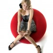 Blonde girl, who sits in a red chair — Stock Photo