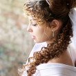 Curly bride against the backdrop of the stone ruins — Stock Photo