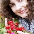 Girl on a background of flowers and fruits dogrose — Stock Photo