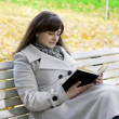 Foto Stock: Girl who reads book in park
