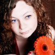 Stock Photo: Beautiful brunette with red gerberas