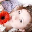 Beautiful brunette with red gerberas — Stock Photo