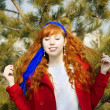 Red curly girl against the backdrop of green trees in a sunny da — Stockfoto