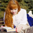 Girl who reads the book in the park — Stock Photo