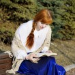 Girl who reads the book in the park - Stock Photo