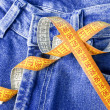 Measuring tape against the backdrop of jeans - Stock Photo