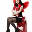 Girl in a devil costume with a gift — Stock Photo