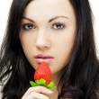 Sexy brunette, who eats strawberries — Stock Photo