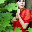 Girl in the red in the green leaves — Stock Photo #7489127