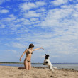 Girl with a dog on the beach — Stock Photo