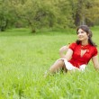 Beautiful girl sitting on the grass — Stock Photo