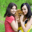 Girls with a dog in the park - Stock Photo