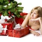 Santa girl lying under the tree — Stock Photo