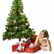 Santa girl lying under the tree — Stockfoto